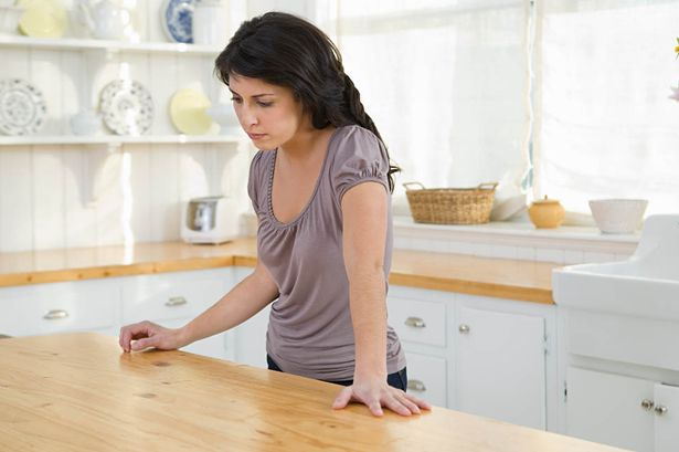 Sad-looking-woman-standing-in-kitchen