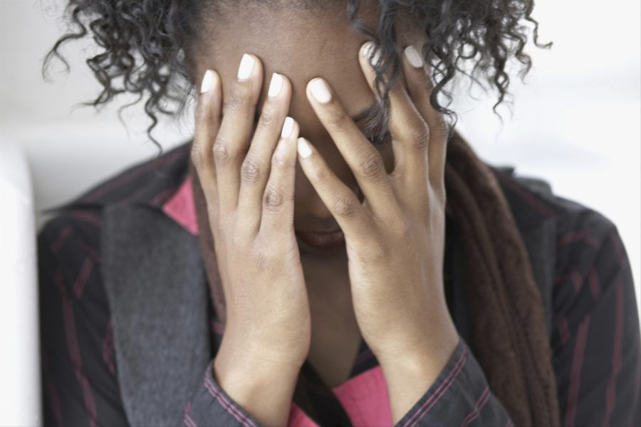 black woman covering face