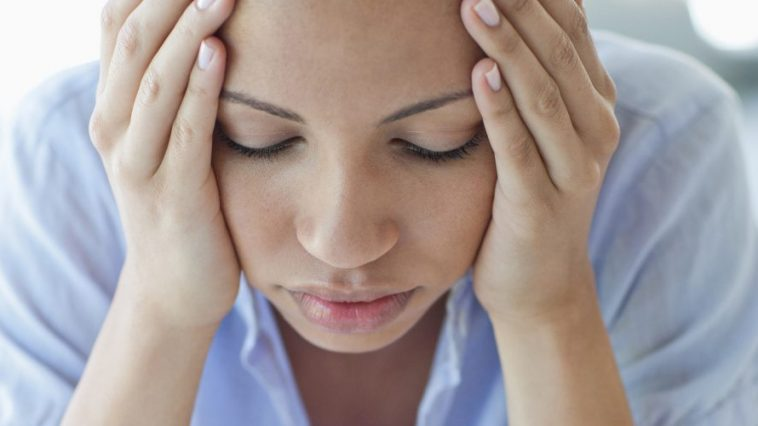 Woman with headache holding head