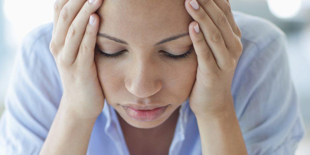 Woman with headache holding head